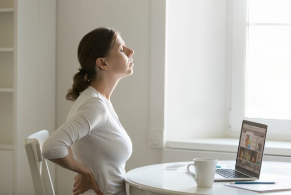 Woman experiencing pain sitting at desk